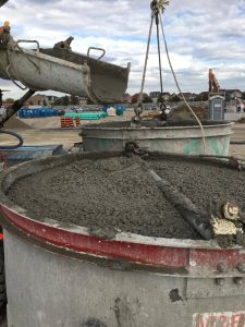 Concrete mixer loading up a crane bucket